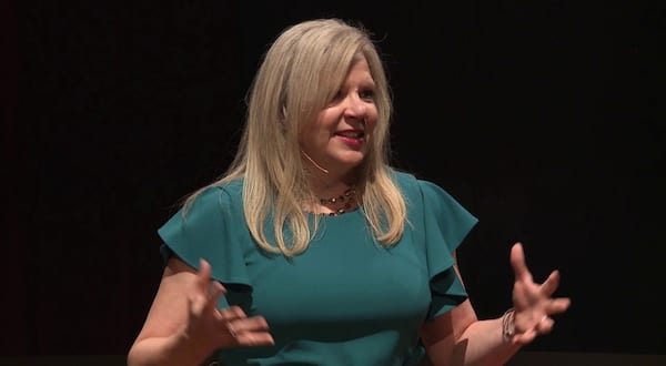 ted talk romance books, image of jessica van slooten a blonde white woman wearing a teal dress, books