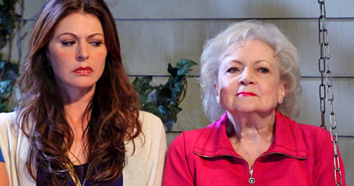 Betty White and Jane Leeves sitting next to each other on a bench in a scene from 'Hot in Cleveland'