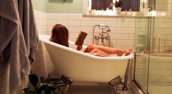 self care books, image of a white blonde woman reading a book in the tub, books