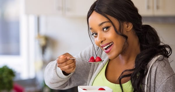 brunette woman eating healthy strawberries from spoon