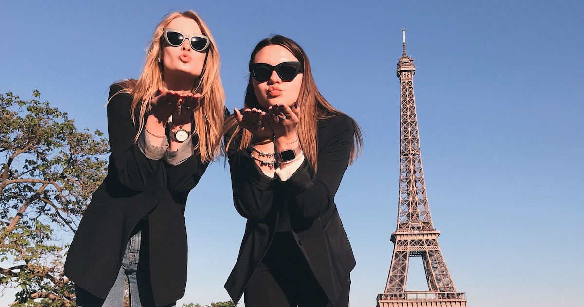 two women wearing black coats blowing kiss posing with eiffel tower in paris france