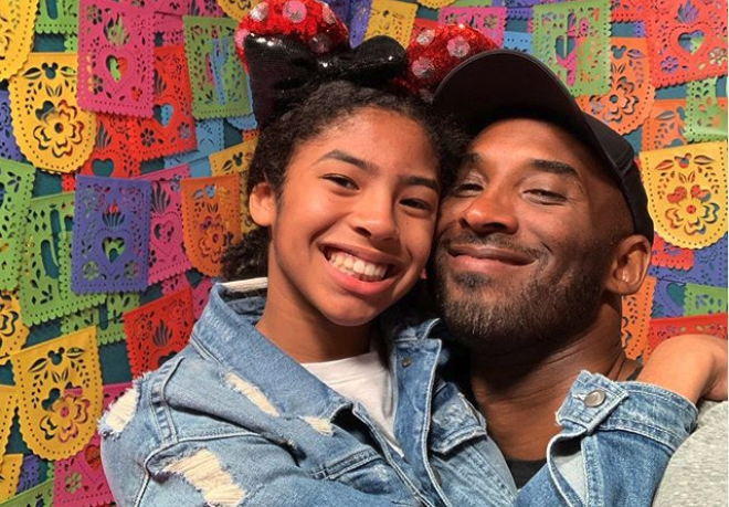 Kobe Bryant and his daughter Gianna smiling in front of a colorful wall