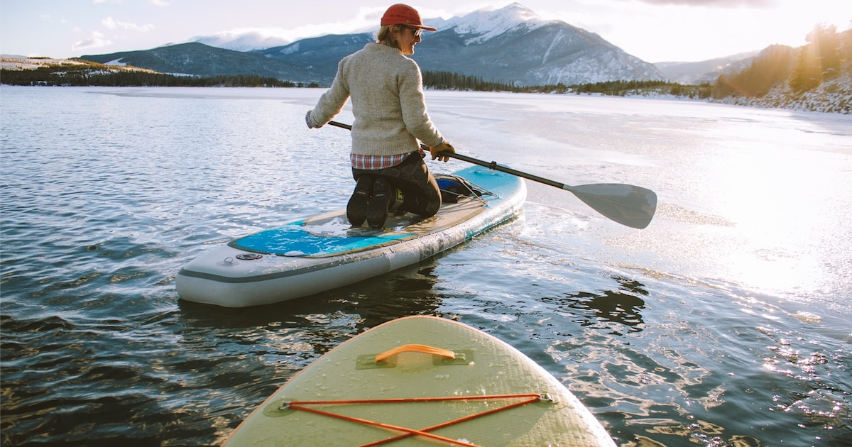 person kneeling on paddle board in water surrounded by mountains