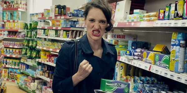 woman holding box of tampons in convenience store