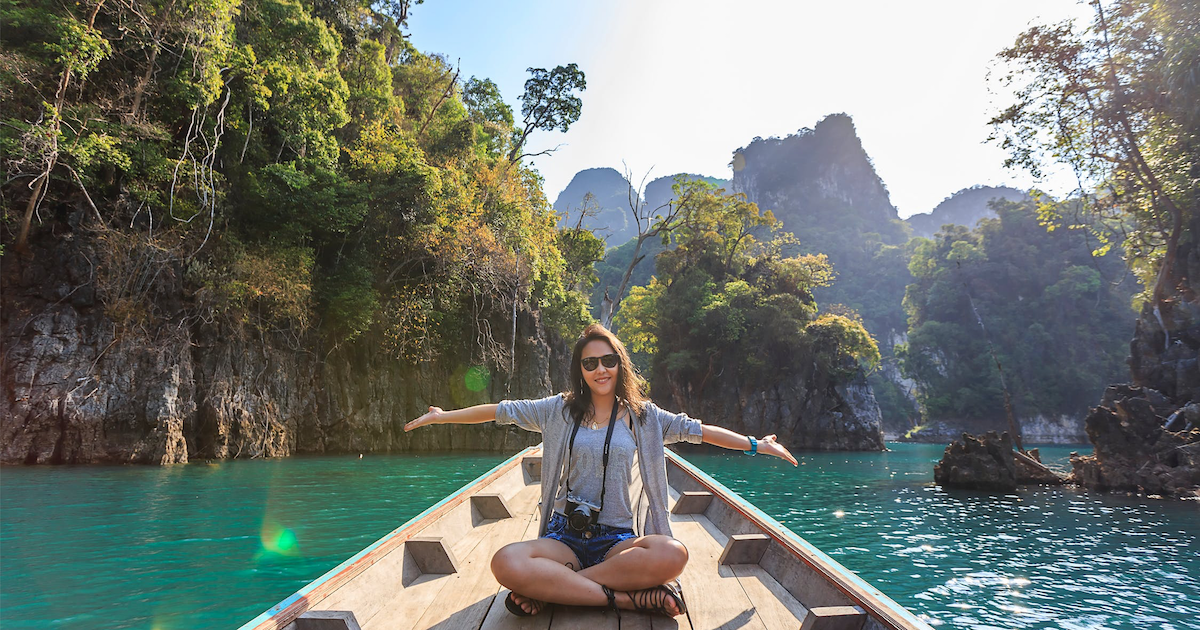 woman with her arms out sitting on small boat in the water surrounded by trees