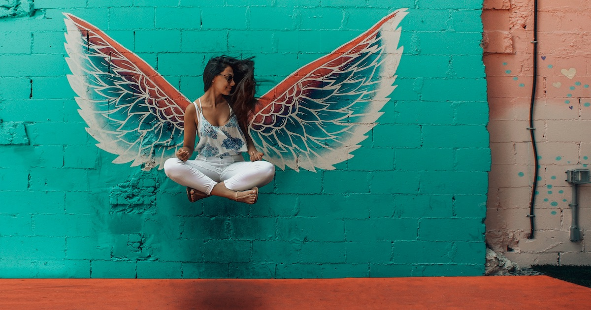 woman sitting in the air against angel wings painting