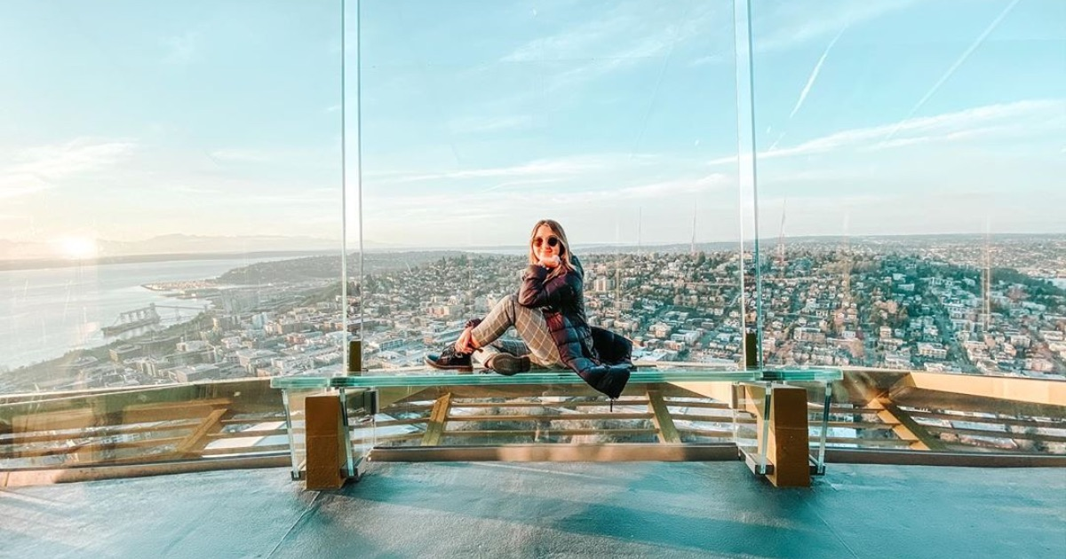 girl sitting at top of space needle in seattle