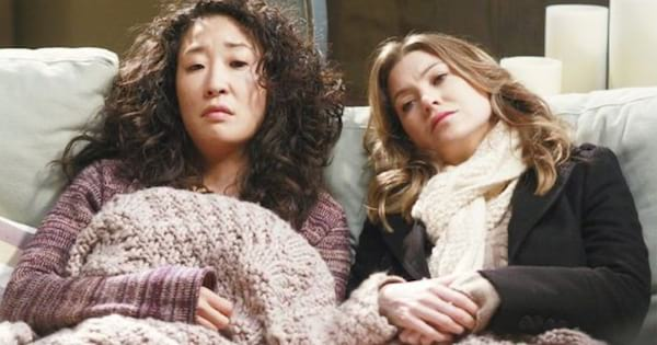 cristina yang and meredith grey sitting on couch comfortable and cozy with blanket