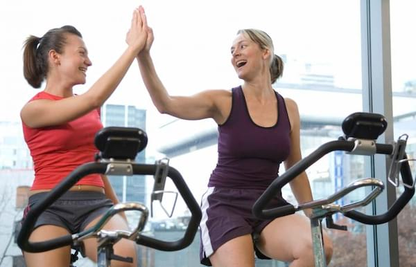 two women on bikes high-fiving