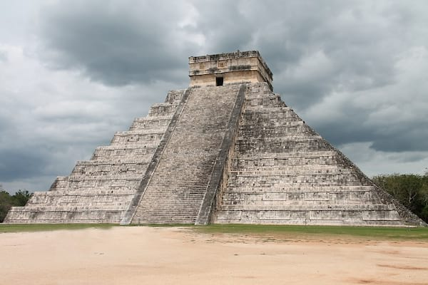 Stone pyramid surrounded with a square-shaped temple on the top surrounded by jungle.