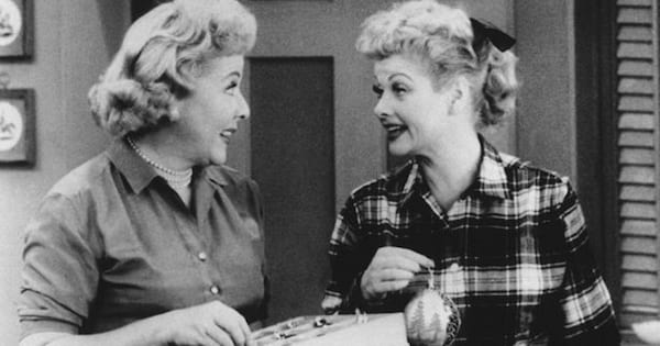 Lucy and Ethel standing together talking.