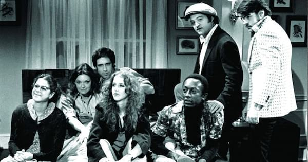 The original cast of Saturday Night Live sitting together for a group photo.