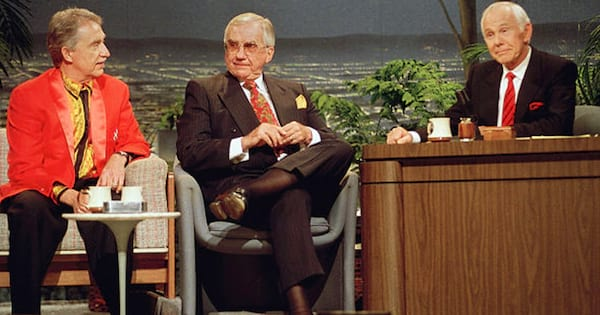 Johnny Carson sitting behind his desk with two guests.