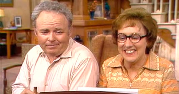 Archie and Edith Bunker sitting behind the piano.