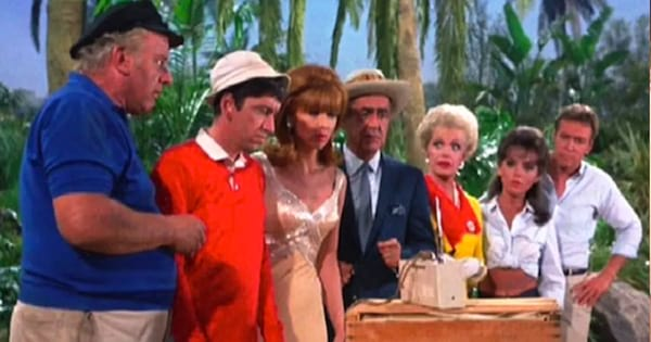 The cast of Gilligan's Island gather together staring at a telephone.