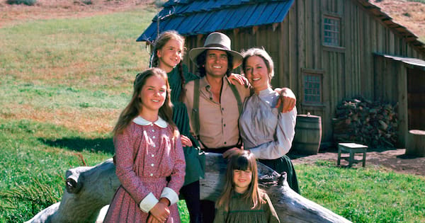 The family happily stands in front of their little house on the prairie.