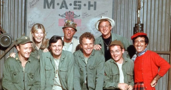 The cast of M*A*S*H stands in front of their logo.