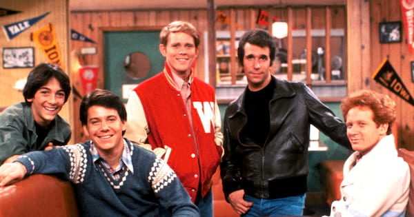 The cast of Happy Days sits in a booth smiling at the camera.