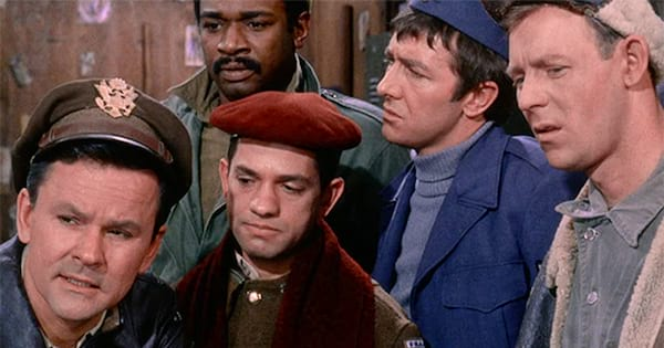 The cast of Hogan's Heroes standing together looking confused.