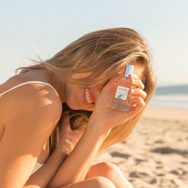 beauty, image of a woman on the beach holding up a bottle of perfume