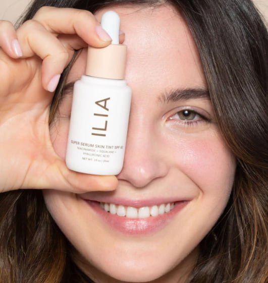 beauty, image of woman holding up a bottle of super serum skin tint