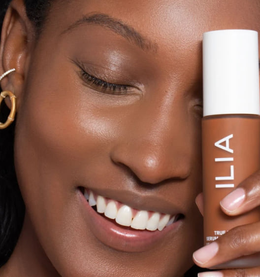 beauty, closeup of a black woman holding a bottle of foundation