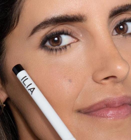 beauty, closeup of a tan woman holding a tube of eyeliner