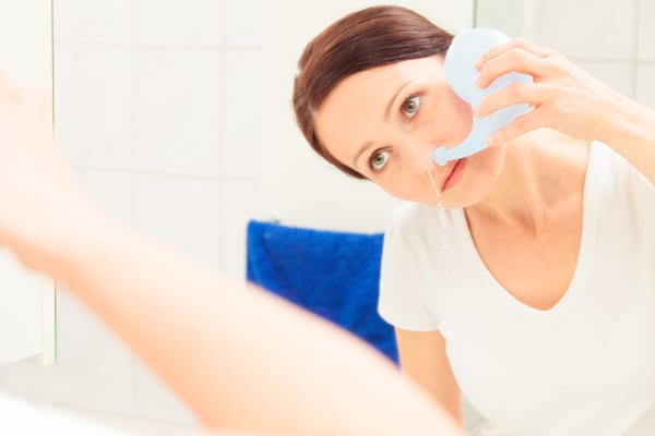 woman using a neti pot for nasal irrigation allergy relief